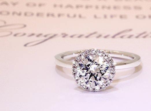 Halo engagement ring on wedding card